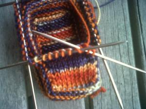 Creating the toe box: I'm knitting across the 10 stitches and the stitch from the side is already on my needle (the blue stitch to the far left) waiting to get knit together with the 10th stitch.