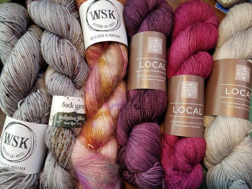 Absolutely beautiful skeins of yarns in greys, purples and magenta.